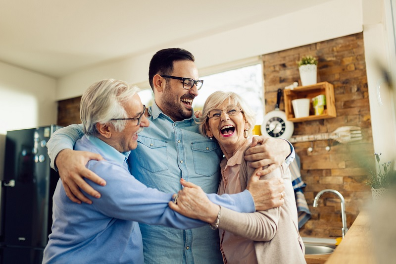 Ritratto di uomo stretto in abbraccio coi genitori anziani