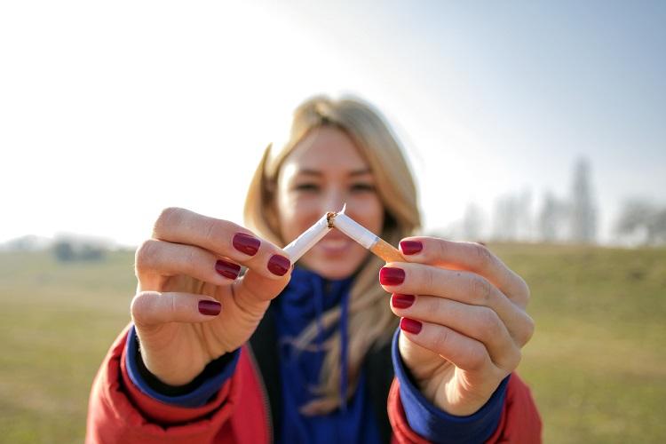 Ragazza con sigaretta spezzata per promuovere lo smettere di fumare