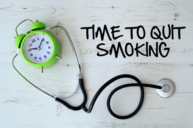 Sveglia collegata a stetoscopio e messaggio di smettere di fumare