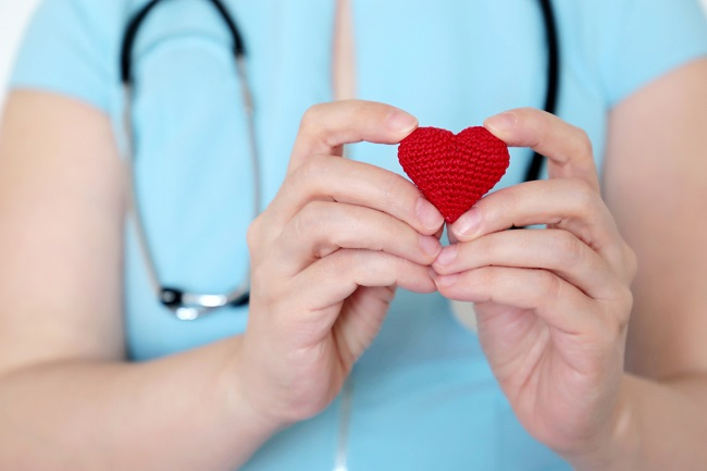 Ritratto di mani di un medico che regge la figura di un cuore