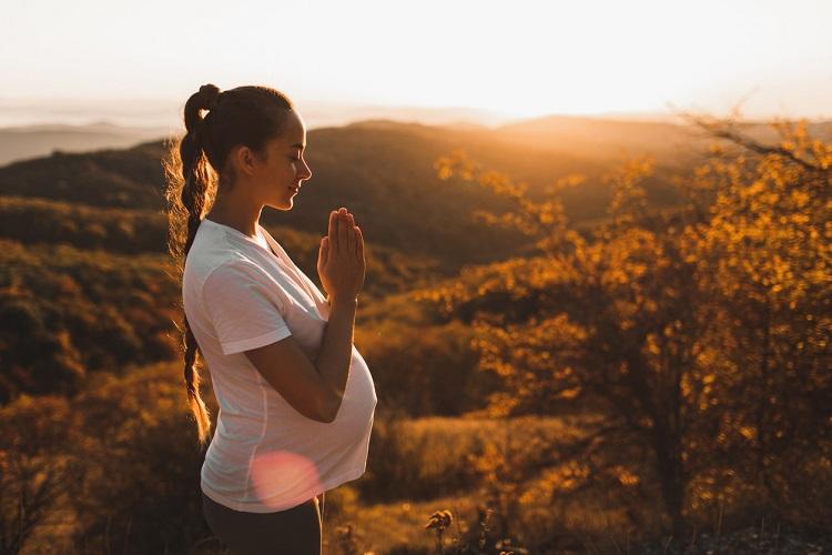 Ragazza in gravidanza di profilo medita in posizione Yoga con paesaggio collinare su sfondo