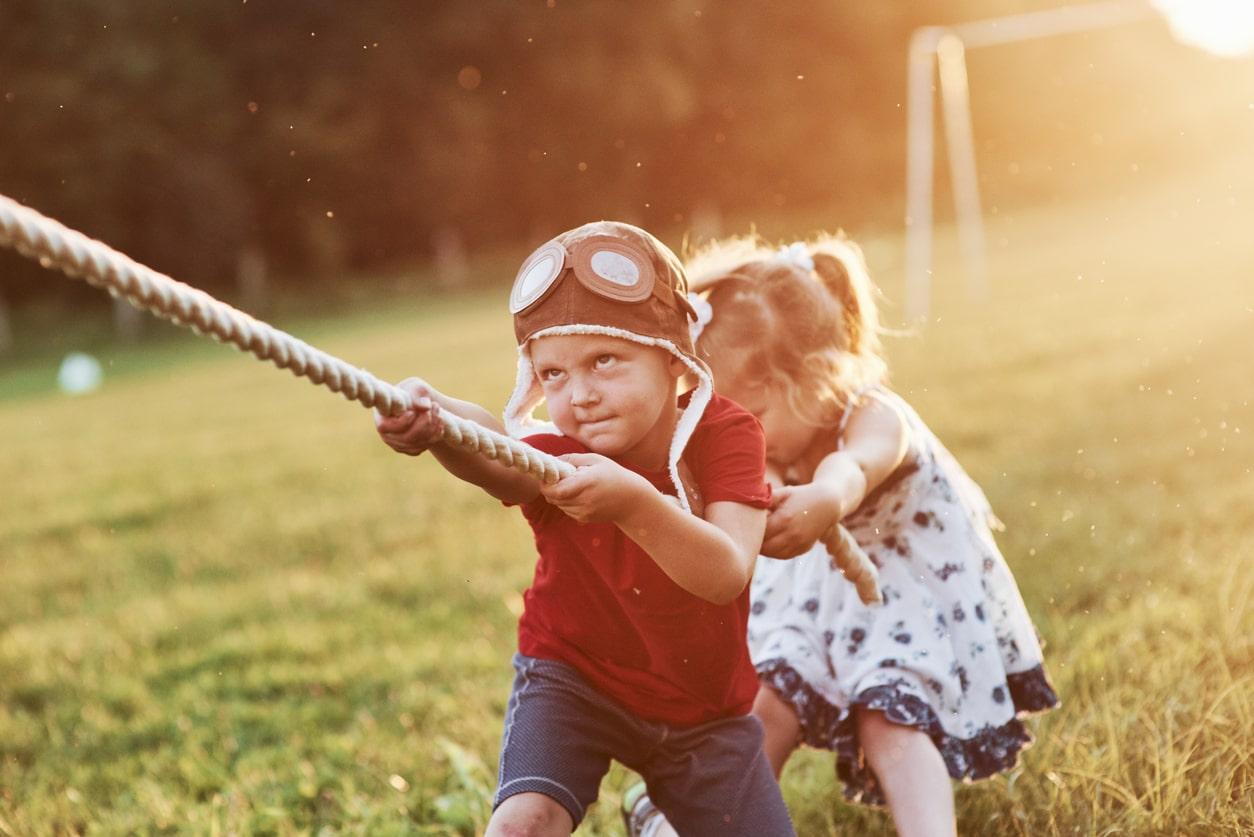 Bambino e bambina tirano luna fune in simbolo di vera amicizia