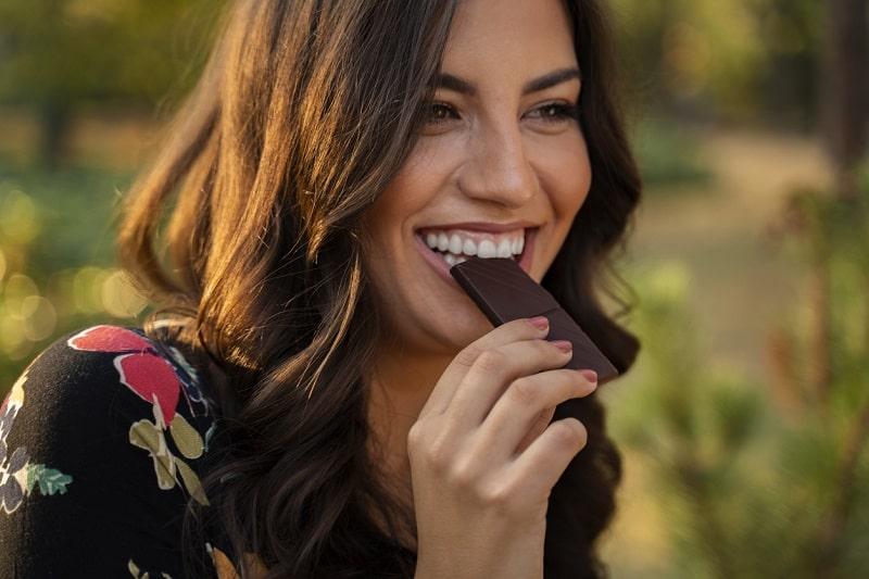 GIovane donna addenta barretta di cioccolato fondente