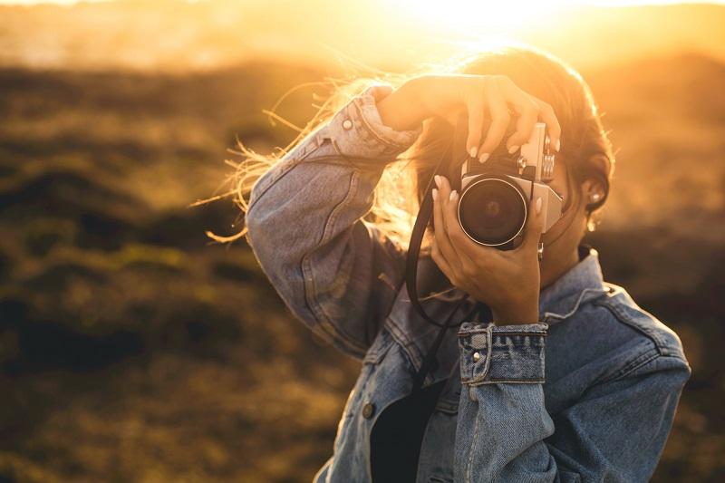 ritratto di ragazza che sta scattando una fotografia con paesaggio solare sullo sfondo