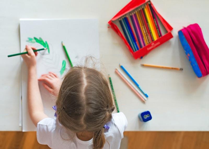 Bambina disegna con matite colorate utilizzando la mano sinistra