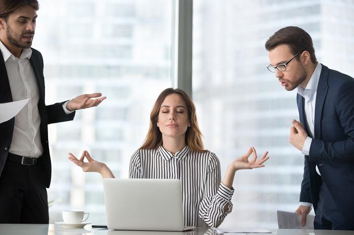 Ragazza in ufficio in posizione meditativa e calma mentre due colleghi manifestano rabbia nei suoi confronti
