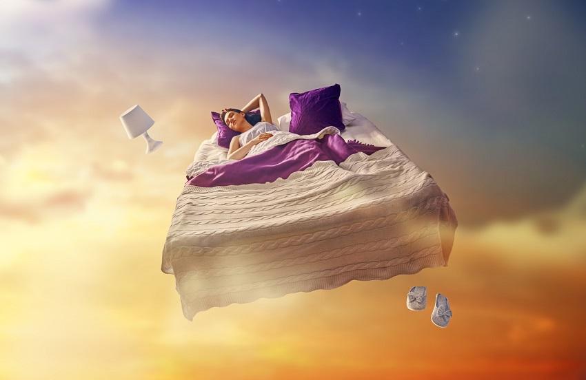 Immagine fantastica di letto volante con ragazza dormiente in cielo crepuscolare