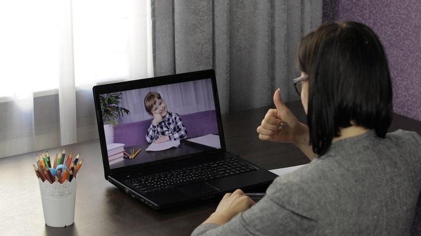 Donna di spalle comunica attraverso videoconferenza su pc portatile con bambino
