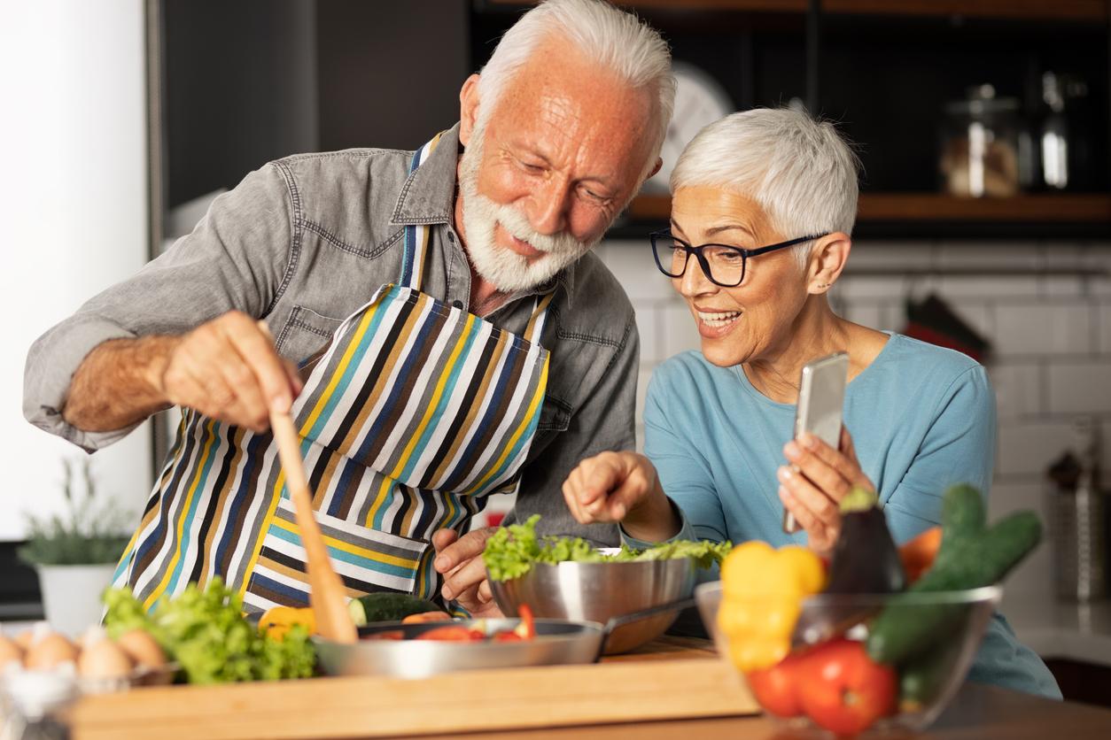 Coppia di anziani cucinano in videochiamata