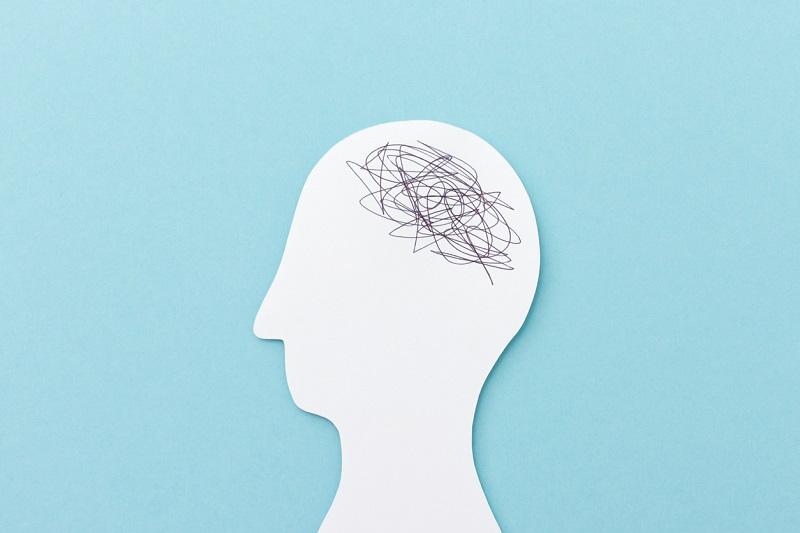 Immagine stilizzata di profilo d'uomo bianco su sfondo azzurro con fili intrecciati a simboleggiare cervello